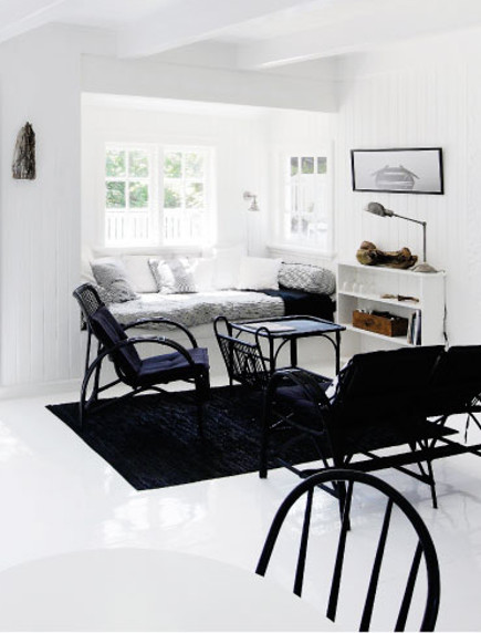 coastal cottage - living room with glossy white-painted floor and black furniture in a Danish coastal cottage in Gilleleje - femina.dk via atticmag