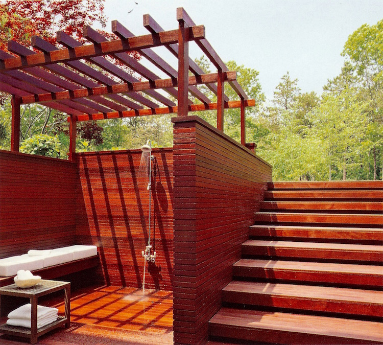 modern outdoor showers - Ipe planked outdoor shower by S. Russell Groves with cushion bench, pergola top and tub filler below the shower head - AD via Atticmag