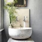 powder room sinks - bowl shaped stone vessel sink on a rustic wood slab - Cico Books via Atticmag