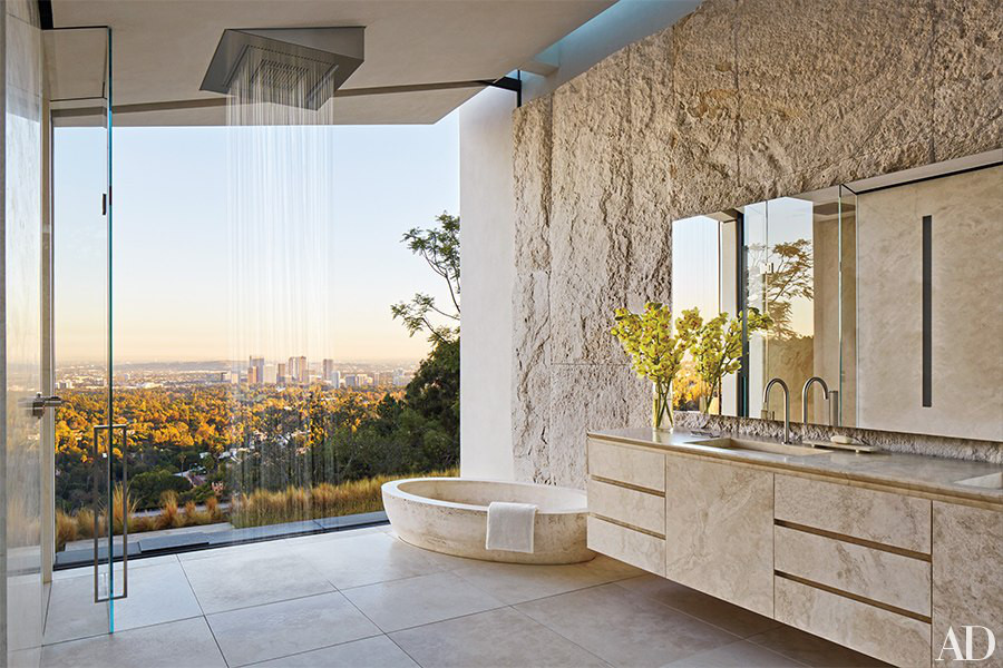 minimalist mansion - Michael Bay's Italian travertine master bath features a low oval tub and Dornbracht rain shower in addition to city views - Architectural Digest via Atticmag