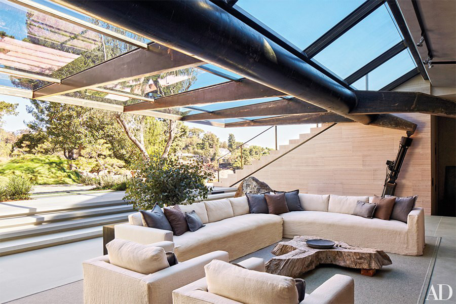 minimalist mansion - Indoor-outdoor room with hydraulic window and James Perse sectional in film maker Michael Bay's L.A. home - Architectural Digest via Atticmag
