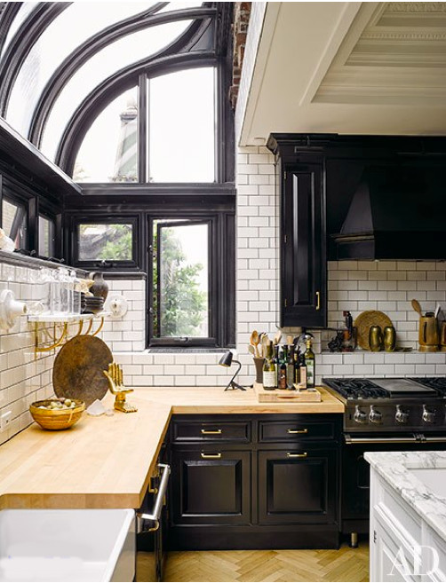 "greenhouse kitchen - ""after"" view of cabinet wall in Nate Berkus and Jeremiah Brent's renovated NYC black and white penthouse kitchen - AD via Atticmag"