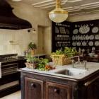 cast iron stove repurposed as a kitchen island with Carrara marble top and prep sink by Studio Peregalli - Elledecor via Atticmag