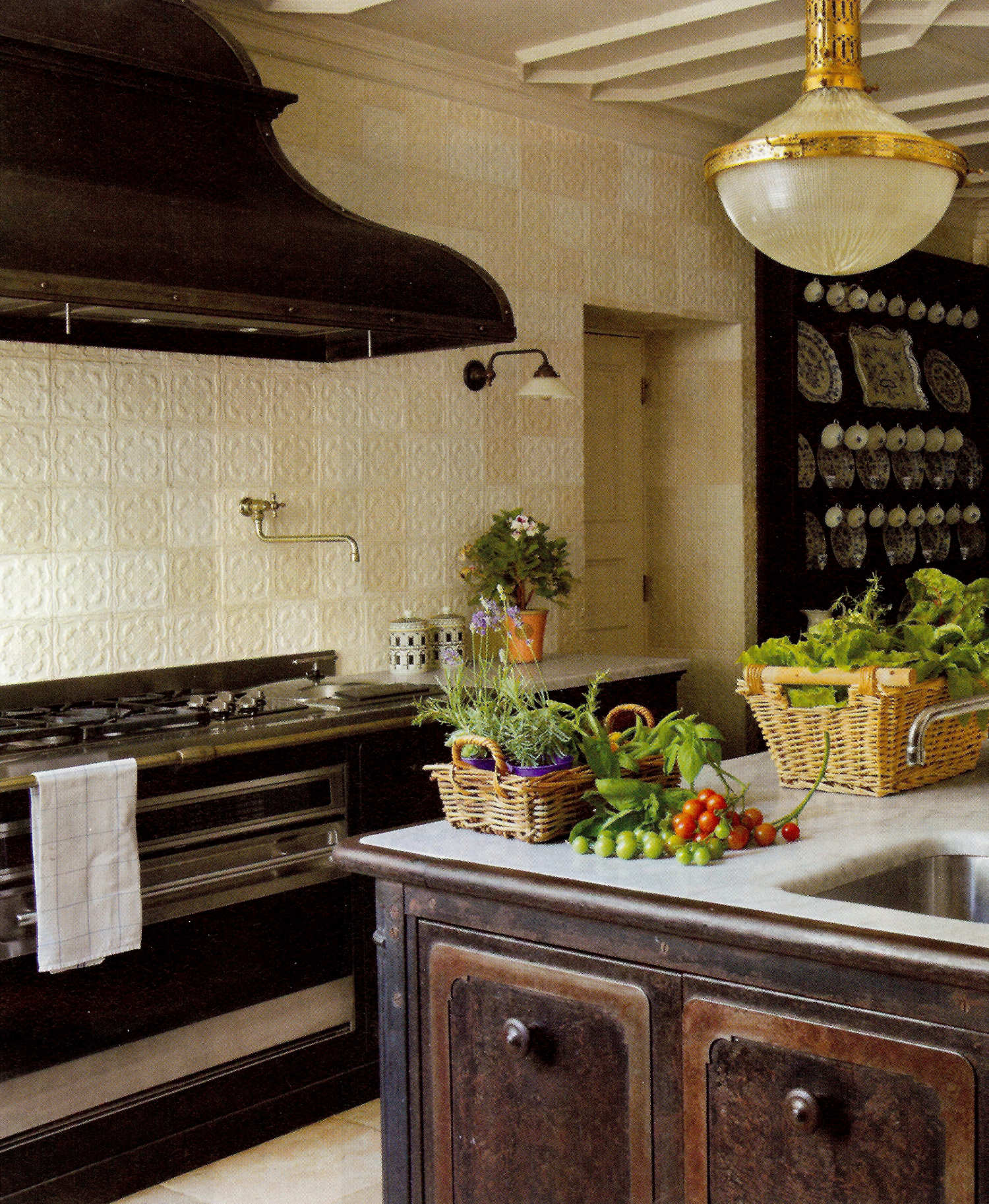 range wall of a Studio Peregalli kitchen with 19th century tile with a cast iron stove repurposed as a kitchen island - Elledecor via Atticmag