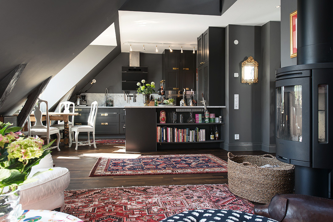 loft kitchen - dark gray Swedish loft kitchen open into living space with oriental rugs and fireplace - AlvhemMakleri.se via Atticmag