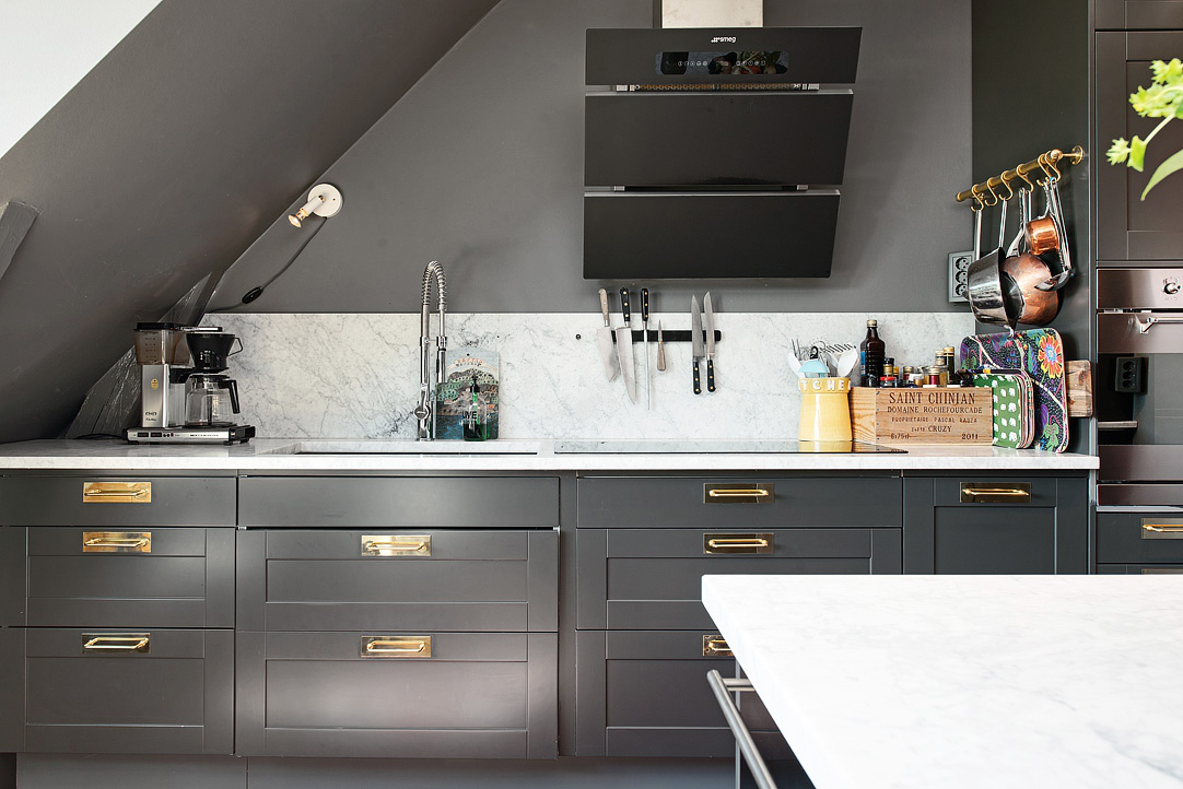 loft kitchen - dark gray Swedish loft kitchen with white marble counters and backsplash, Smeg vent hood and induction cooktop - AlvhemMakleri.se via Atticmag