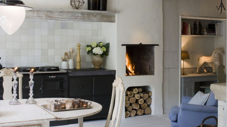 belgian kitchens - white kitchen with antique Swedish dining table, upholstered armchair, fireplace and Aga cooker- Joris van Apers via Atticmag