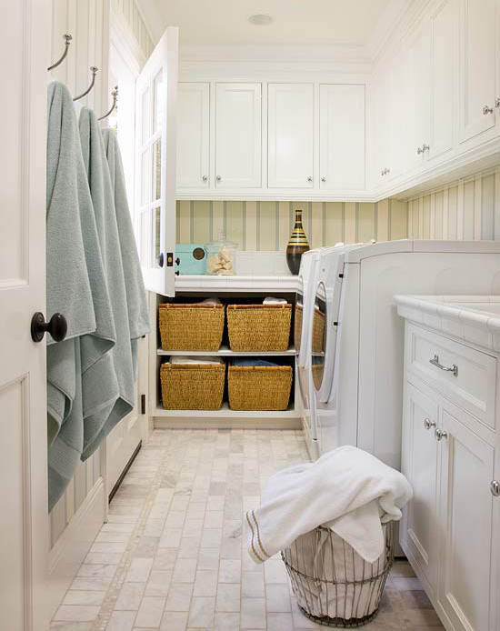 laundry room baskets - white laundry room with Dutch door and open base cabinet storage for 4 laundry baskets - BH&G via Atticmag