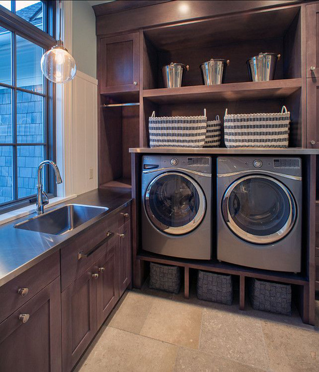 laundry room baskets - a fitted laundry room with washer/dryer on rises and basket above and below the machines - Scott Christopher Homes via Atticmag