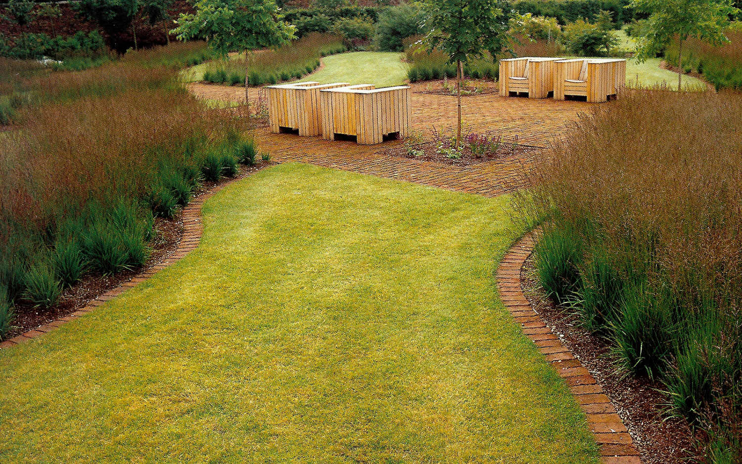 walled gardens - section of the Scampston walled garden planted with beds of purple moor grass and brick seating areas - House & Garden via Atticmag