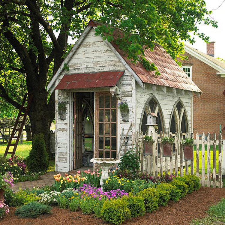 backyard shed - White-painted shed with salvaged Gothic church windows used as a garden shed and art studio - Better Homes and Gardens via Atticmag