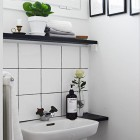 contrasting tile and grout in a Swedish bathroom with white square field tile and black grout - Stadshem.se via Atticmag