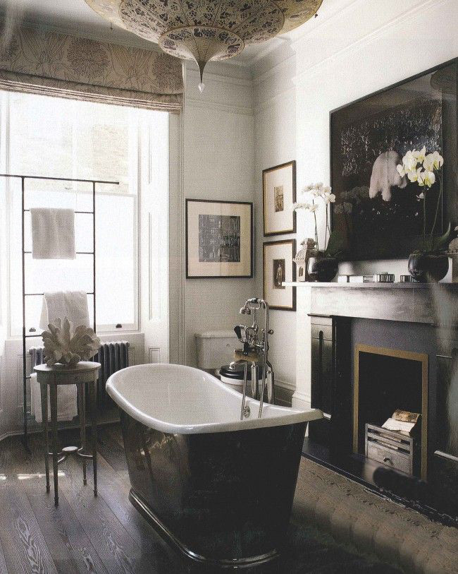 traditional bathroom fireplaces - handsome dark antique wood-burning fireplace in a formal bath with freestanding tub - elledécor via atticmag