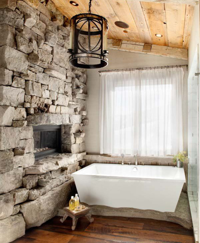 traditional bathroom fireplaces - Montana stone wall bathroom with inset gas fireplace - peacedesign via atticmag