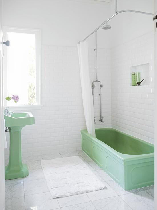 green bathrooms - jadeite vintage pedestal and bathtub in an all-white subway tile and marble bath - remodelista via atticmag