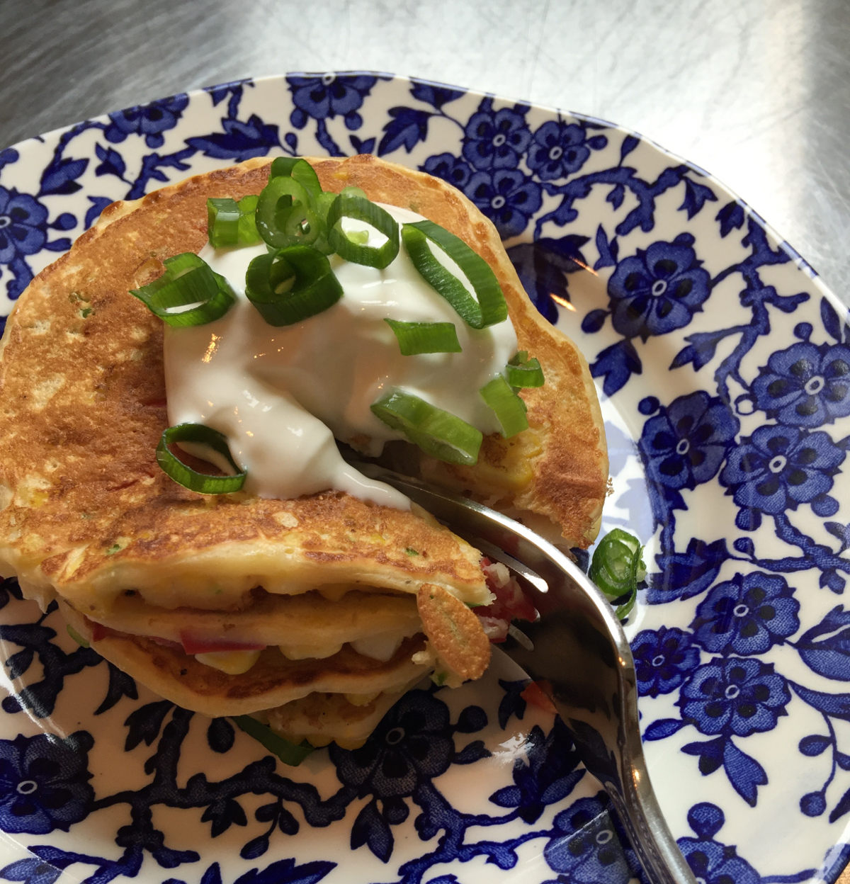 corn and jalapeño pancakes - a tall stack of vegetable pancakes garnished with sour cream and scallion greens - Atticmag.com