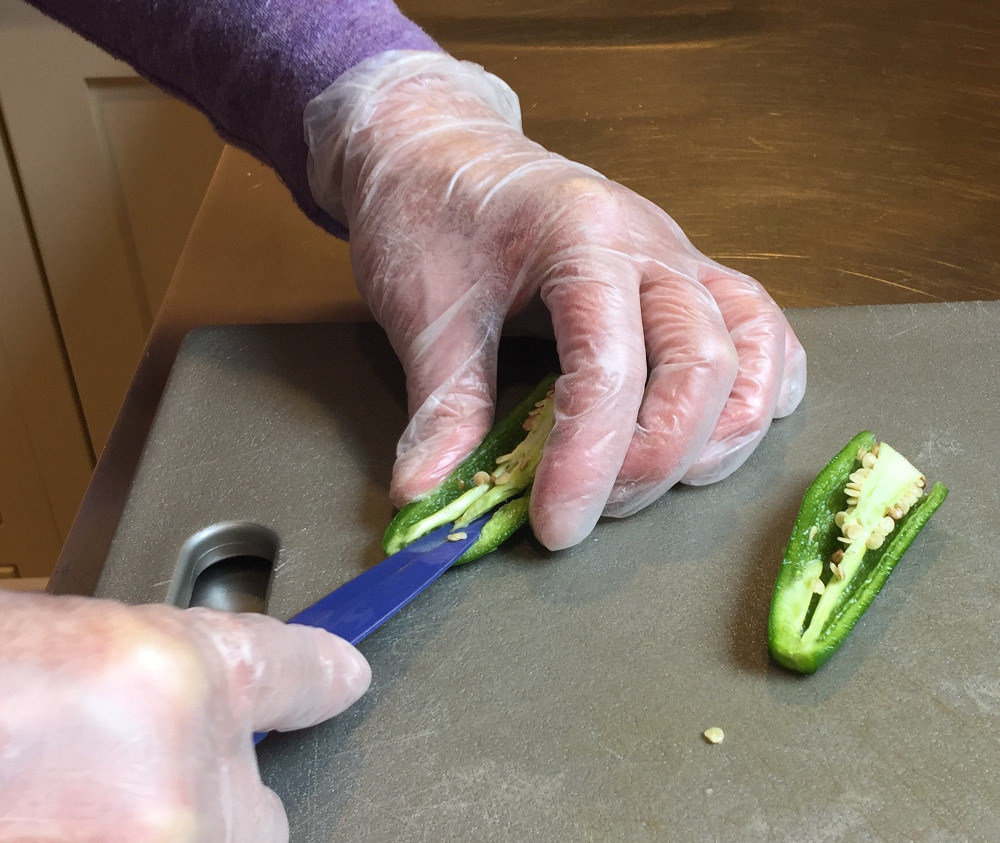 removing ribs and seeds from jalapeño peppers for Thai Taste Cole Slaw - atticmag.com