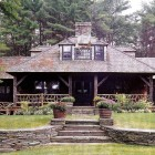 fishing camp - front view of the house with Adirondack twig porch railings and bench - Country Living via Atticmag