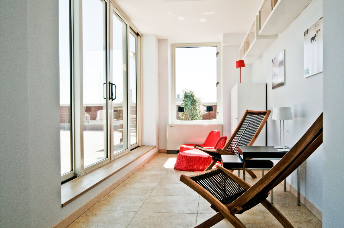 Ikea penthouse - indoor seating area on the terrace level with chairs and Solig solar lamps - Craig Paulson via Atticmag