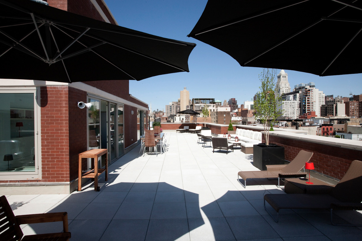 Ikea penthouse - outdoor terrace with umbrellas and furniture allow the owners to have an enormous outdoor entertaining space - Craig Paulson via Atticmag