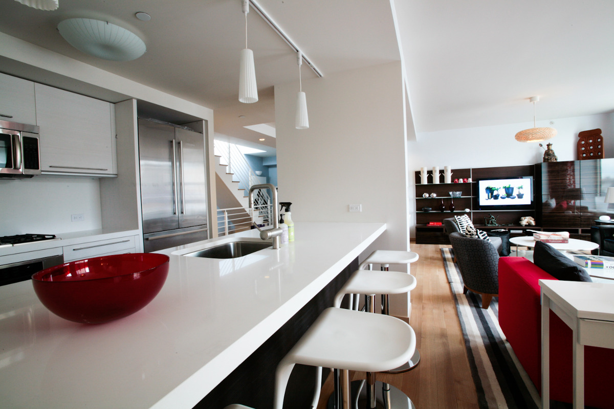 Ikea penthouse - kitchen open to the living room with Liebherr refrigerator and builder appliances - Craig Paulson via Atticmag