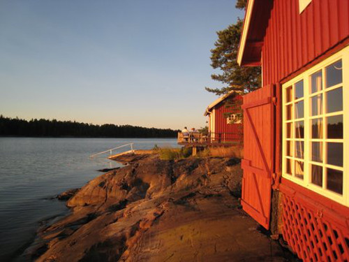 scandinavian summer house - red painted out building overlooking the ocean - Atticmag