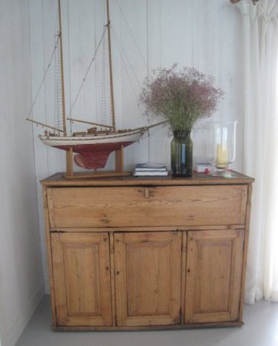 scandinavian summer house - antique writing desk with a ship's model and guest book on the top - Atticmag