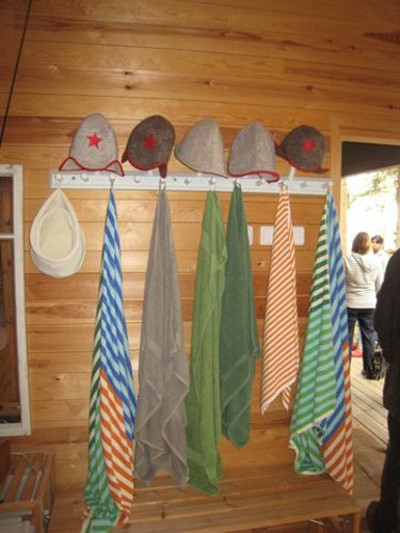 scandinavian summer house - towels and felt hats are hung up so guests can use them to stay warm after leaving the sauna - Atticmag