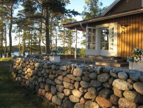scandinavian summer house - outdoor dec buttressed by stone dry walls built by Estonian masons - Atticmag