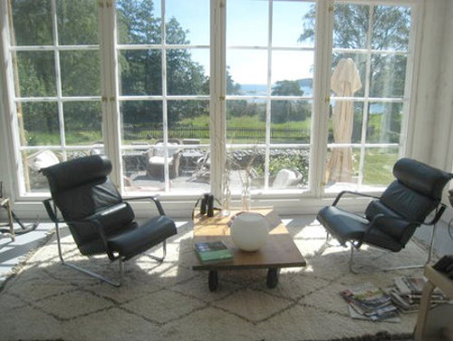 scandinavian summer house - leather chairs on a Berber rug by a window overlooking the grounds - Atticmag
