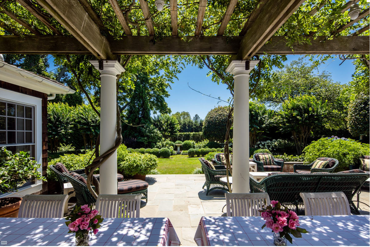 DeRose Windmill Cottage - covered patio of the historic Victorian house with attached windmill - Brown, Harris Stevens via Atticmag