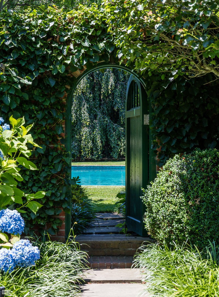 DeRose Windmill Cottage - gate set in a brick wall around the pool of the historic Victorian house with attached windmill - Brown, Harris Stevens via Atticmag