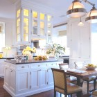 double sided glass cabinets - white kitchen with glass upper cabinets over the island - Ferguson & Shamamian via Atticmag