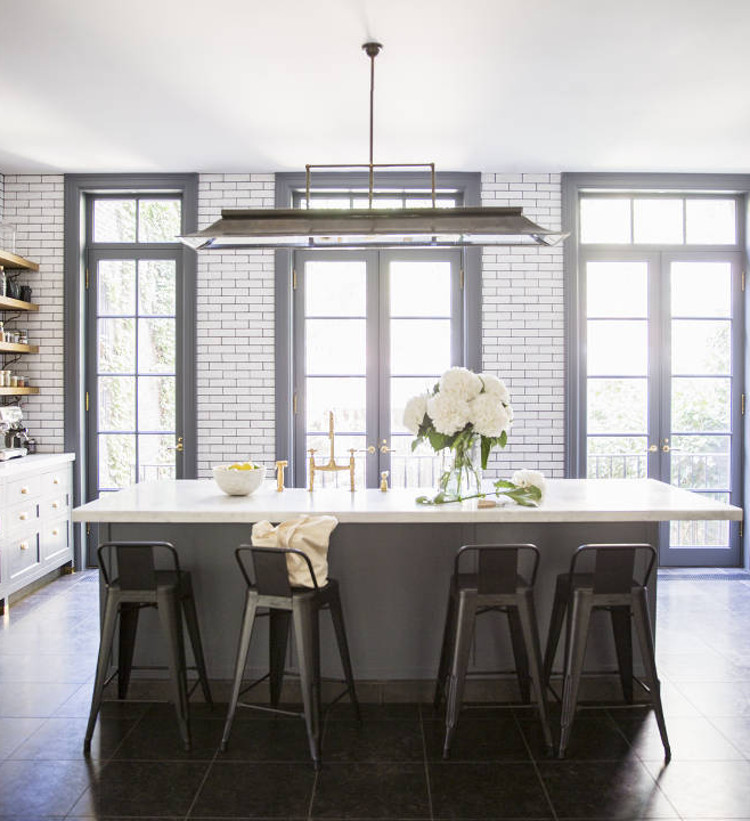 subway tile eurosplash - gray kitchen with white subway tile and black ground used floor to ceiling on a garden window wall - domino via atticmag