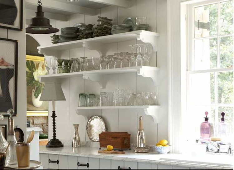 open kitchen shelves - white-painted wood shelves with ogee brackets over painted wood paneling adjacent to a sink - bill litchfield via atticmag