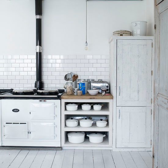 open kitchen shelves - open base cabinet shelves for cookware storage between an Aga cooker and a pantry cupboard - living etc via atticmag
