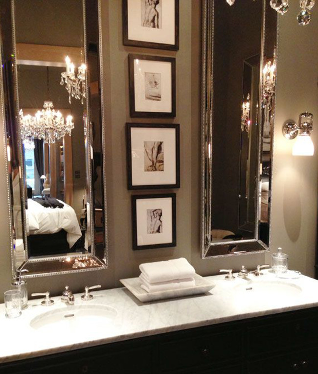bathroom picture walls - two sizes of black-framed sepia prints hand between a pair of vertical mirrors over a double vanity - nathaliabessa.com.br via atticmag