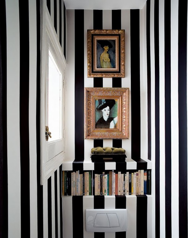 bathroom picture walls - narrow black and white striped powder room with small gilded paintings - spearmintdecor via atticmag