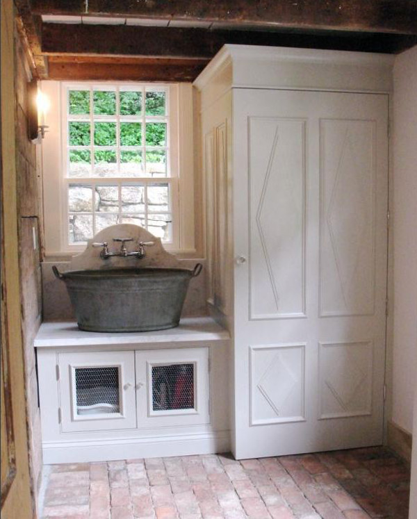 custom laundry room - washtub basin sink with a marble counter and backsplash plus an enclosed laundry closet with diamond panel designs - salisbury artisans via atticmag