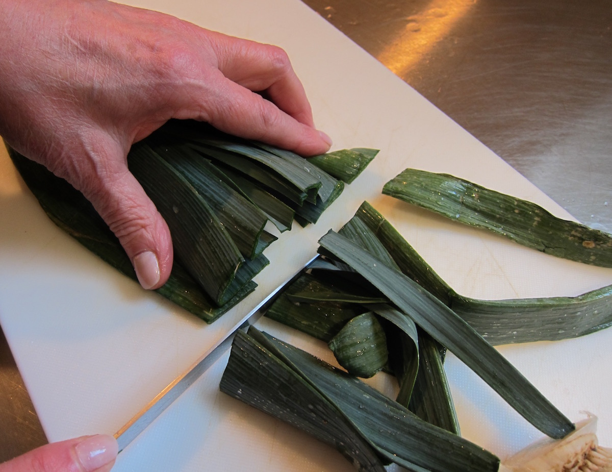 two soups in one bowl - preparing a leek by cutting off the green dry tips - Atticmag