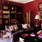 plummy dark rooms - living room with purple sofa and deep red walls by Paolo Moschino - House & Garden via Atticmag