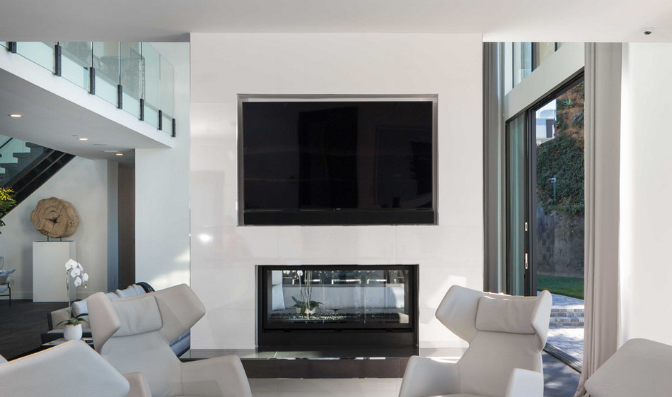 modern mansion - double sided glass fireplace with built in flat screen TV in Beverly Hills home designed by Kirk Nix purchased by Chrissy Teigen & John Legend - KNA Design via Atticmag
