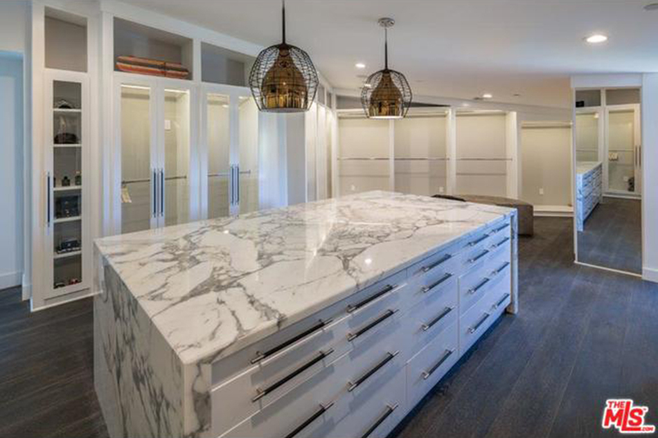 modern mansion - marble island with storage drawers in the closet of the Beverly Hills home designed by Kirk Nix purchased by Chrissy Teigen & John Legend - MLS via Atticmag