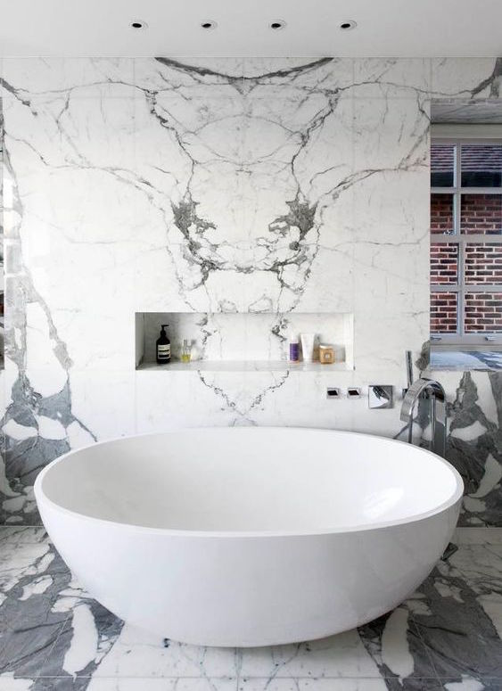 white marble bath with bookmatched tiles on the wall and floors - housetohome.co.uk via Atticmag