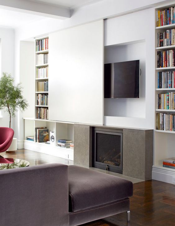 hidden tvs - flat screen concealed in a recessed niche over a fireplace and covered by a sliding panel made to look like the wall - The NY Times via Atticmag