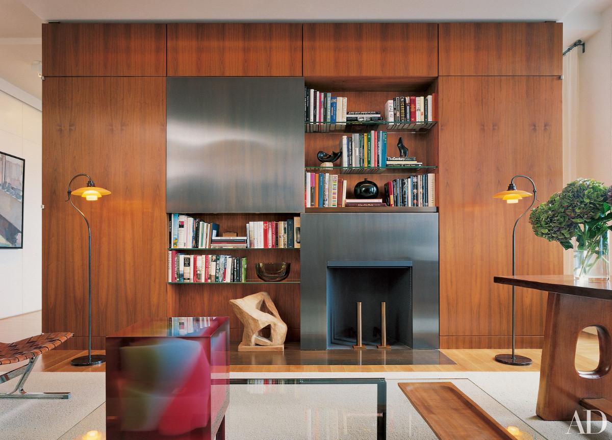 hidden tvs - TV concealed behind a sliding bronze pane set into a wood partition cabinet in a New York apartment study by Shelton Mindel & Assocs. - AD via Atticmag