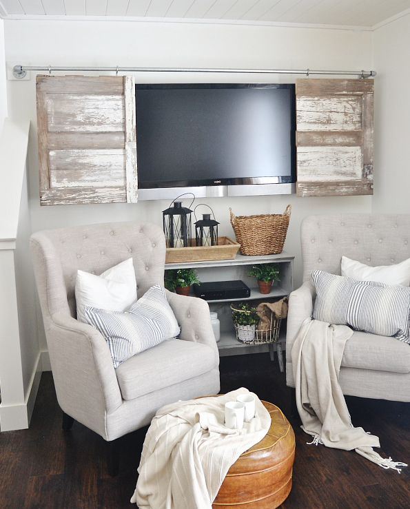 hidden tvs - Sliding vintage barn style doors hung on a DIY plumbing pipe track - Liz Marie Blog via Atticmag