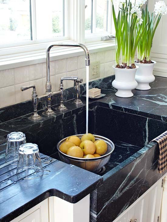nearly black apron front soapstone sink with runnels and matching soapstone counters in a white kitchen - BH&G via Atticmag
