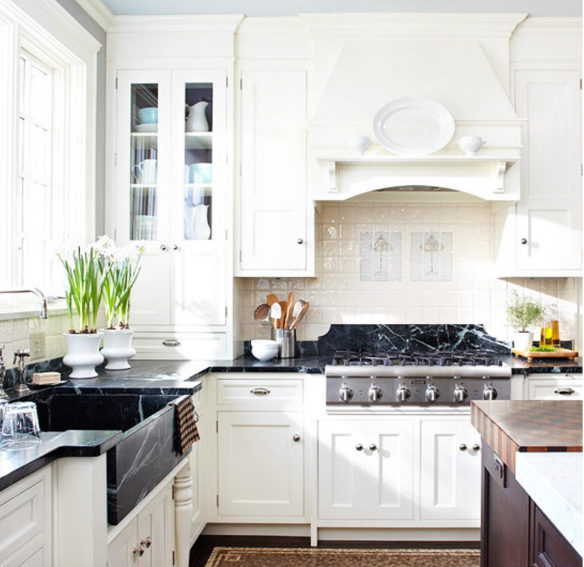 white traditional kitchen with a nearly black apron front soapstone sink and matching counters plus a soapstone detail behind the range top - BH&G via Atticmag