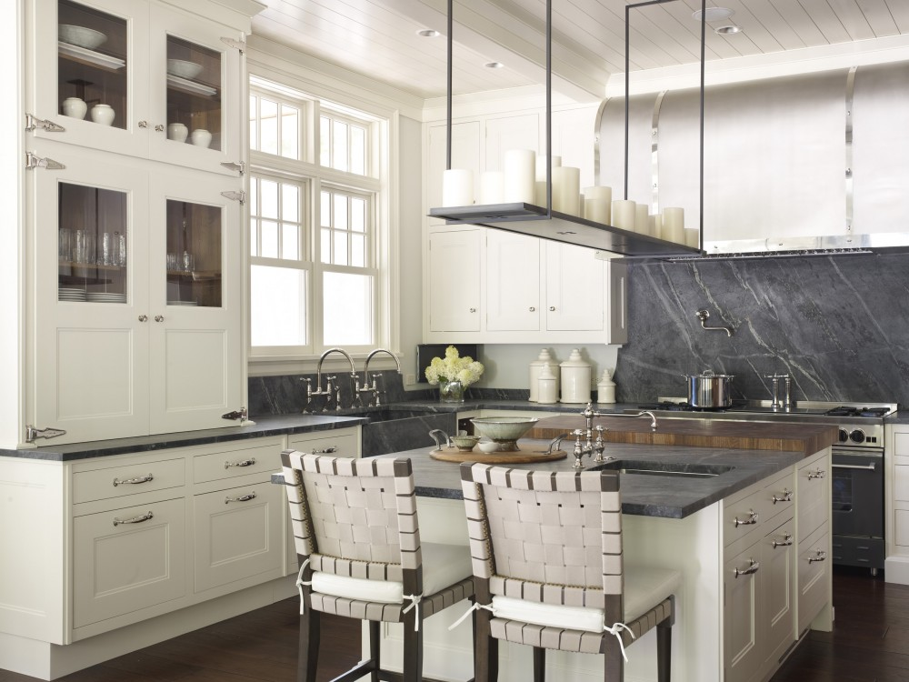 large steel gray custom apron front soapstone sink with a pair of faucets in a Lake Geneva, Wisc. white transitional kitchen with period details - Hickman Interiors via Atticmag